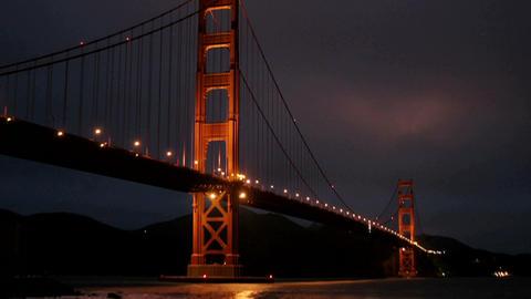 San Francisco's Golden Gate Bridge is illuminated in a darkening sky Footage