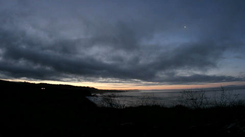 Dark clouds move quickly over a shoreline as the sky... Stock Video Footage