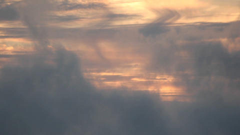 Clouds move quickly across a colorful sky as it darkens Stock Video Footage