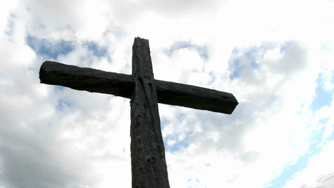 A cross in silhouette stands beneath swiftly moving clouds in a blue sky Footage