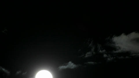 A bright full moon rises above swiftly moving clouds in... Stock Video Footage