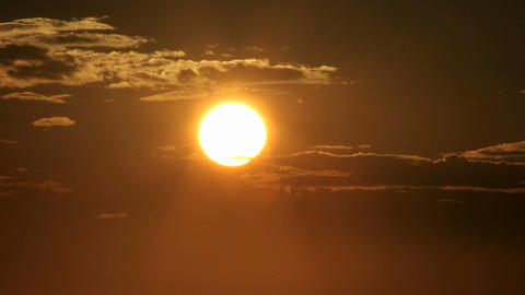 A glowing orange sky darkens as the sun slips below the... Stock Video Footage