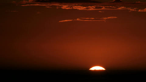 A glowing orange sky darkens as the sun slips below the... Stock Video Footage