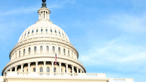 The white dome of the United States Capitol Building contrasts against a blue sky Footage