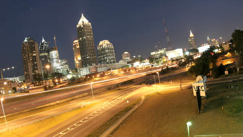 Lights brighten in downtown Atlanta, Georgia and its surrounding highways as evening changes to nigh Footage