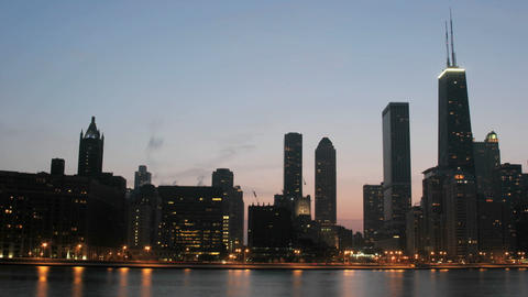 Lights brighten as the sky darkens in downtown Chicago Footage