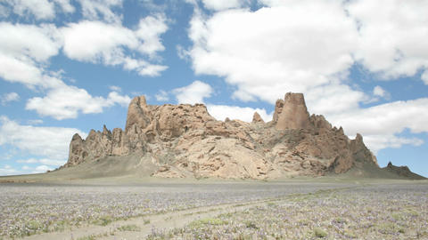 Fluffy white clouds pass over New Mexico's Shiprock Footage