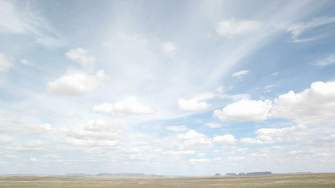 Time lapse shot of white clouds moving over the desert in... Stock Video Footage