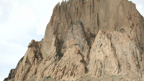Shadows and sunlight alternate as clouds pass over New Mexico's Shiprock Footage