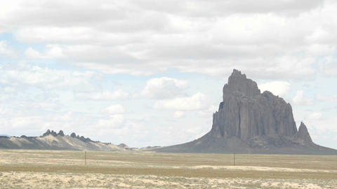 Shadows and sunlight alternate in the valley near New Mexico's Shiprock Footage