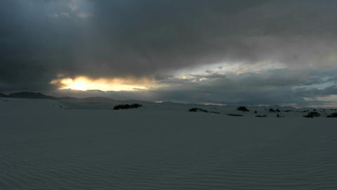 The sun lends a fiery golden glow on the horizon of White Sands National Monument, gradually fading Footage