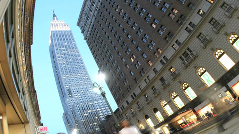 The Empire State Building is framed by blue sky as accelerated traffic and pedestrians pass in the f Footage