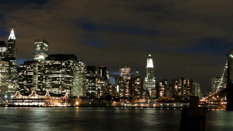 Slow pan of a time-lapsed view of the Brooklyn Bridge and the New York City skyline from golden-hour Footage