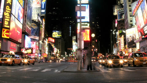 Shot slowly pans right in an accelerated shot of traffic and pedestrians in New York's Times Square Footage