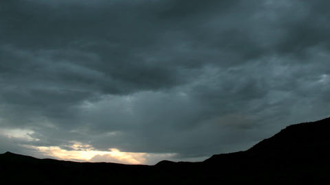 Slow pan as golden light flares at the horizon beneath dark storm clouds Footage