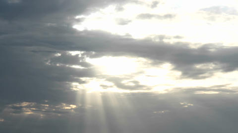 Sun halations shine through as a bright gold sun disappears behind dark clouds Live Action