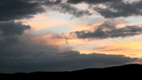 A gold and orange sky intensifies in color as it is obscured beneath dark clouds Footage