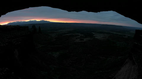 Bright light pierces the dark horizon during golden-hour at Mesa Arch in Canyonlands National Park Footage