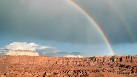 A rainbow glows in the sunlight as it arches over Goblin Valley State Park Footage
