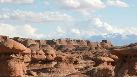 Slow pan of white clouds floating in a blue sky over Goblin Valley State Park Footage