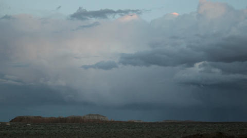Storm clouds in the golden-hour take on muted shade of pink and blue, then fade into darkness Footage