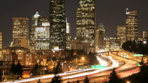 Accelerated traffic blurs into streaks of light before an illuminated Seattle skyline Live Action