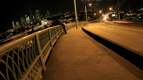 Pedestrians and traffic cross a bridge in Seattle at night Stock Video Footage