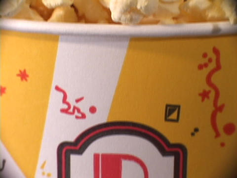 Pan-down of a full container of popped corn Stock Video Footage