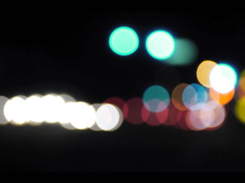 An accelerated selective-focus shot of traffic lights at an intersection that pans-down to city traf Footage
