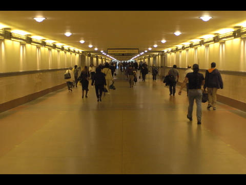 An accelerated medium shot of a multitude of people walking down an indoor walkway Footage