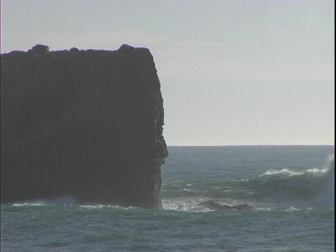 Medium shot of a huge rock being battered by ocean waves Stock Video Footage
