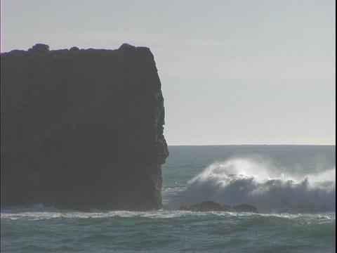 Medium shot of a huge rock being battered by ocean waves Stock Video Footage