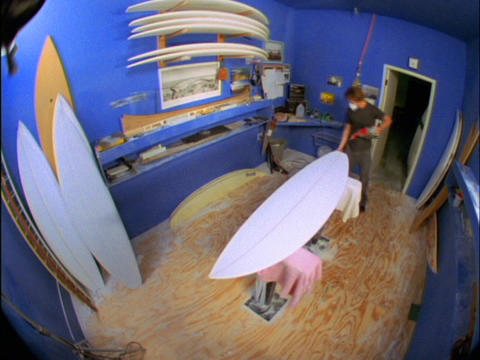 A fish-eye view of a man in a blue room building surfboards Stock Video Footage