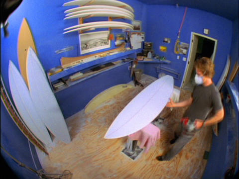 A fish-eye view of a man in a blue room building surfboards Footage