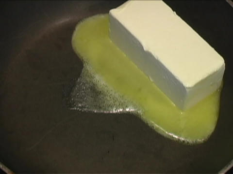 A cube of butter melts and sizzles in a frying pan Stock Video Footage