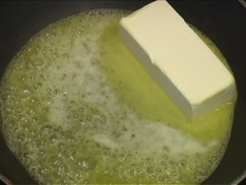 A cube of butter melts and sizzles in a frying pan Footage