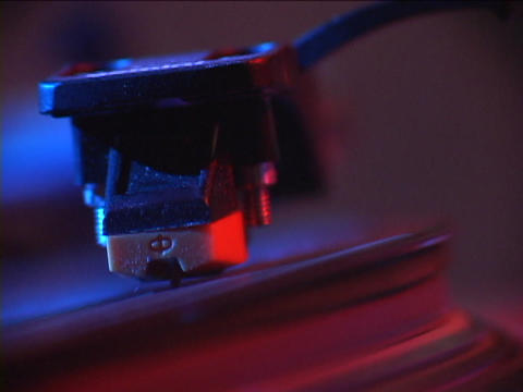A record player tone arm moves across a vinyl record Footage
