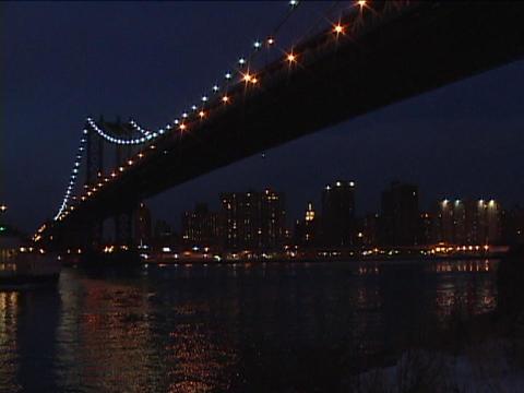 A passenger boat sails beneath a bridge at night Stock Video Footage