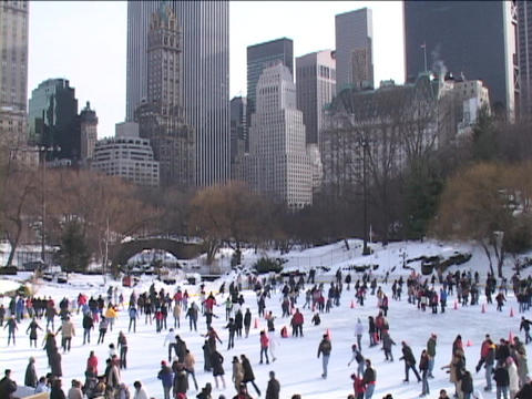 New Yorkers ice skate on a frozen lake in Central Park Stock Video Footage