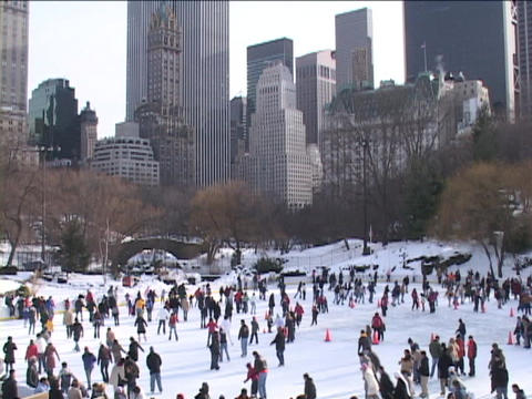 New Yorkers ice skate on a frozen lake in Central Park Footage