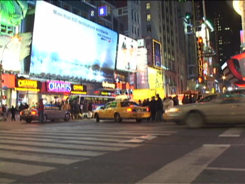 Traffic crosses through a busy intersection in Manhattan at night Footage