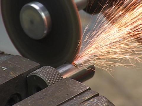A saw cuts a large metal bolt Footage