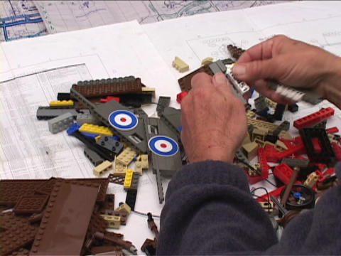 An artist assembles a Lego biplane Stock Video Footage