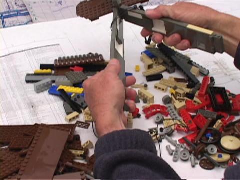 An artist assembles a Lego biplane Stock Video Footage