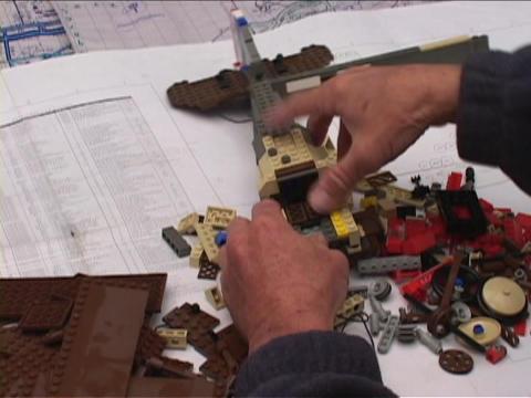 An artist assembles a Lego biplane Footage