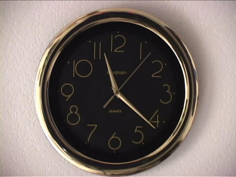 Hands spin quickly on a clock Live Action