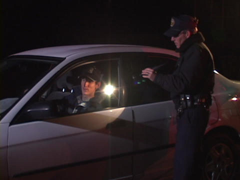 A police officer walks up to a car that he has pulled over and talks with the man inside Footage