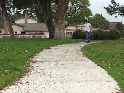 A boy skateboards down the sidewalk Stock Video Footage