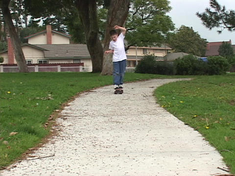 A boy skateboards down the sidewalk Live Action