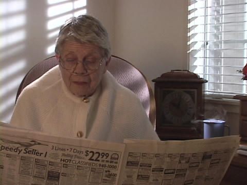 An older woman reads the newspaper as her coffee cup emits steam Footage